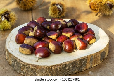 Chestnuts on the old wooden and rustic table. Fresh sweet chestnut. Food background.