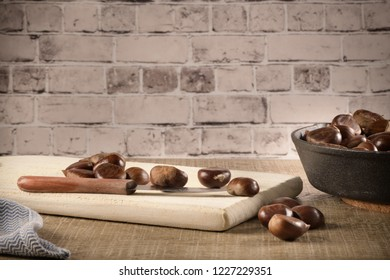 Chestnuts on wooden cutting board.