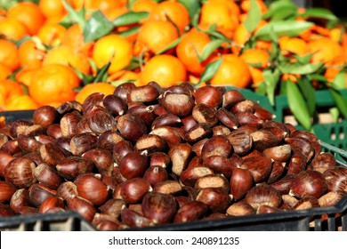 Chestnuts and Oranges both harvested in Greece at Christmas are shown piled together at a Market stall in Irepetra, Crete