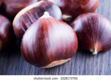 Chestnuts over wooden table, close up, horizontal image