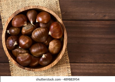 Chestnuts in wooden bowl, photographed overhead on wood with natural light (Selective Focus, Focus on the chestnuts on the top)