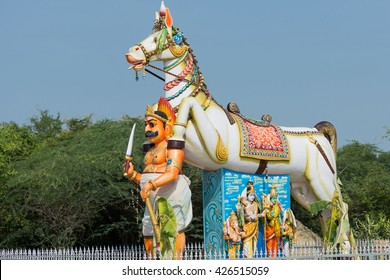 Chettinad, India - October 16, 2013: Ayyanar and his horse at his shrine in Pilivalam village.Tableau of Lord Shiva family under the horse belly. Blue sky.