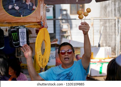 Cheung Chau, Hong Kong - 22 May 2018: A food stall owner spend hard effort to sell his straw of fishballs.