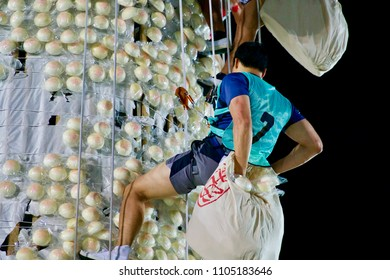 Cheung Chau, Hong Kong - 22 May 2018: The competitor wearing a luck 7 shirt in Bun Scrambling Competition, scramble up and try to collect as many 'lucky' buns as possible.