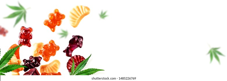 Chewing candies, marmalade with CBD oil and THC. Colored marmalades fly along with cannabis leaves. Colorful creative background, minimalism.