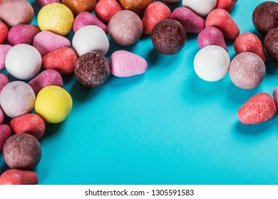 chewing gum, candies of different colors and other sweets on a blue background