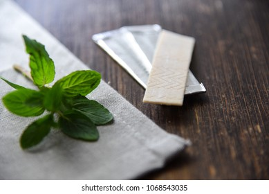 Chewing gums with mint leafs on wooden table