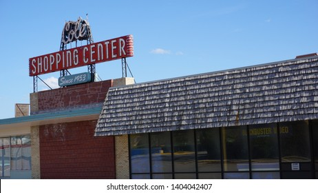 Cheyenne, Wyoming - April 27, 2019: Cole Shopping Center sign with closed Blockbuster Video store.