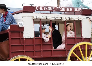 Cheyenne, Wyoming - July 27, 2019: Cheyenne Frontier Days carriage in a CFD parade. This red and white carriage with yellow wheels features a family riding in authentic attire.
