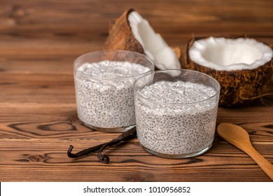 chia pudding in glass, decorated  vanilla pods, spoon and coconuts on wooden background, diet healthy eating and weight loss concept