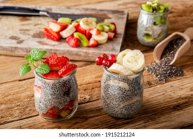 Chia pudding in glass jar stawberry banana kiwi on wooden plank