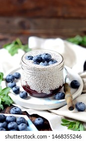 Chia pudding with jam and blueberries on a dark wooden table