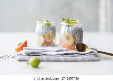 chia pudding in jars with apricot, banana and gooseberry on a white kitchen table. nutrition, healthy food