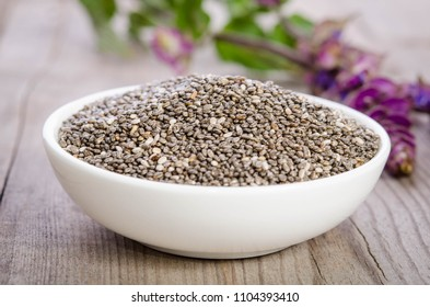 Chia seed healthy superfood in bowl with flower over wooden table
