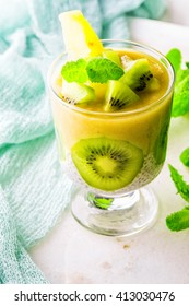 Chia seed pudding pineapple banana smoothie in a glass decorate kiwi white stone table. Healthy yellow smoothie  organic raw fruits on a fresh mint background.  Detox, diet, vegetarian food concept.