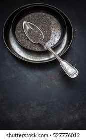 Chia seeds in a bowl of metal and a spoon on an old rusty metal background