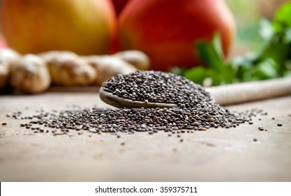 Chia seeds on a wooden spoon with apples, ginger and greens in the background
