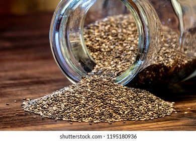 Chia seeds on a wooden table with a glass