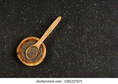 Chia seeds in organic dish on dark concrete background. Top view. Healthy food concept.