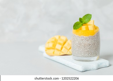 Chia seeds pudding with mango puree in beautiful glasses with green mint leaves and cut fresh ripe tropical fruit on light gray background - raw vegetarian sweet organic dessert.