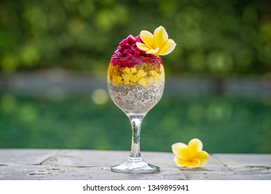 Chia seeds pudding with red dragon fruit, passion fruit, mango and avocado in a glass for breakfast on the background of the swimming pool water, close up. The concept of healthy eating.