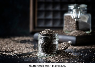 Chia seeds in small glass jar, gray background, selective focus