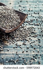 Chia seeds in a wooden scoop on a wooden rustic background