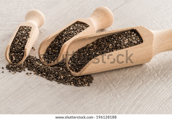 Chia seeds in wooden scoops on wooden table.