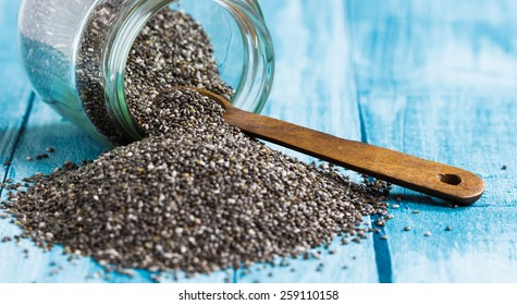 Chia seeds with wooden spoon on blue background, selective focus