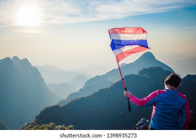 Chiang Dao, Chiang Mai, Thailand - February 2019 : Asian trekking woman holding Thailand flag at the top of wildlife sanctuary name Doi Luang Chiang Dao with Shadow of mountain layer and sun ray.