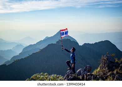 Chiang Dao, Chiang Mai, Thailand - February 2019 : Asian trekking man holding Thailand flag at the top of wildlife sanctuary name Doi Luang Chiang Dao with Shadow of mountain layer and sun ray.