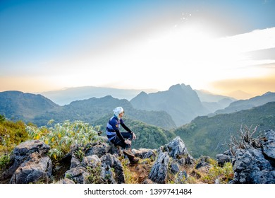 Chiang Dao, Chiang Mai, Thailand - February 2019 : Asian Backpacker trekking acting over sky at wildlife sanctuary name Doi Luang Chiang Dao with Shadow of mountain layer and sun ray.