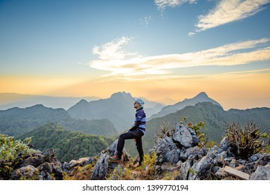 Chiang Dao, Chiang Mai, Thailand - February 2019 : Asian Backpacker trekking acting over Golden sky at wildlife sanctuary name Doi Luang Chiang Dao with Shadow of mountain layer and sun ray.