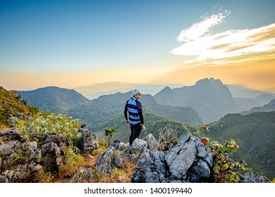 Chiang Dao, Chiang Mai, Thailand - February 2019 : Asian Backpackers trekking waiting golden sunset sky at wildlife sanctuary name Doi Luang Chiang Dao with Shadow of mountain layer and sun ray.