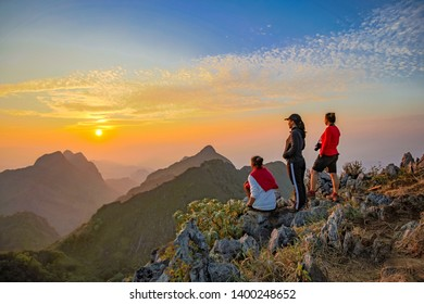 Chiang Dao, Chiang Mai, Thailand - February 2019 : Three Asian Backpacker trekking acting over golden cloud at wildlife sanctuary name Doi Luang Chiang Dao with Shadow of mountain layer and sun ray.