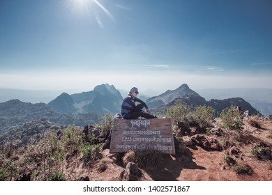 Chiang Dao, Chiang Mai, Thailand - February 2019 : Asian Backpackers trekking Sitting on label post of wildlife sanctuary name Doi Luang Chiang Dao with Shadow of mountain layer and sun ray.