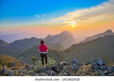 Chiang Dao, Chiang Mai, Thailand - February 2019 : Asian Backpacker trekking Standing over sky at wildlife sanctuary name Doi Luang Chiang Dao with Shadow of mountain layer and sun ray.