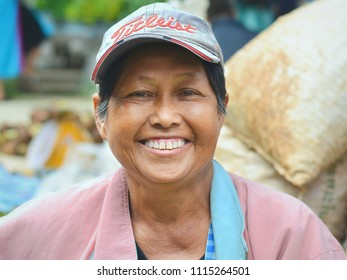 CHIANG DAO, THAILAND - NOV 17, 2015: Smiling elderly Thai market woman with baseball cap poses for the camera at the village's country market, on Nov 17, 2015.