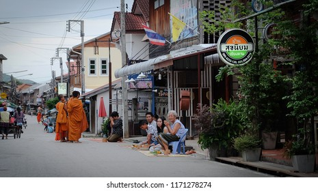Chiang Khan, Loei, Thailand - Circa August, 2018 : Thai monks go with a bowl to receive food or Sticky rice from tourist in early morning at ChiangKhan Walking street, Loei Province,Thailand.