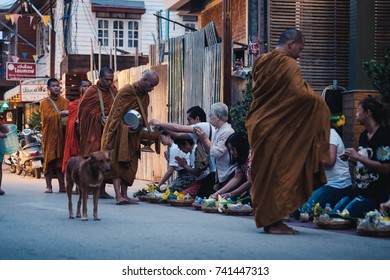 CHIANG KHAN, THAILAND - OCTOBER 15, 2016: Unidentified people offer sticky rice to Buddhist monks in the morning in Chiang Khan, Thailand.