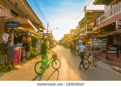 Chiang Khan,Loei / Thailand - Oct 12 2018 : Tourists walking and cycling in walking street of retro village during the long weekend at Chiang Khan district, Loei province.