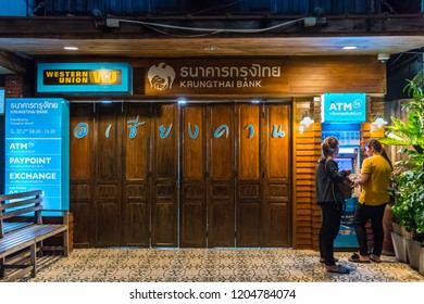 Chiang Khan,Loei/Thailand - Oct 12 2018 : Female tourists are using a bank ATM decorated with a retro style office building in harmony with the environment at Chiang Khan district, Loei province.