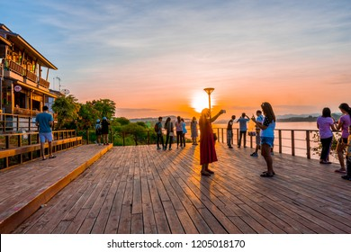 Chiang Khan,Loei/Thailand - Oct 12 2018 : Tourists taking a picture and stand admiring beautiful sunset along the Mekong River of retro village during the long weekend at Chiang Khan district, Loei