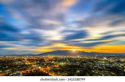 Chiang Mai cityscape at twilight from a high angle with light of building and Doi Suthep as a background, Clouds moving shot.