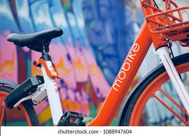 CHIANG MAI - MAY 12, 2018: orange bicycle in bike sharing project, scan and ride by mobike with colorful graffiti as background at chiang mai, thailand