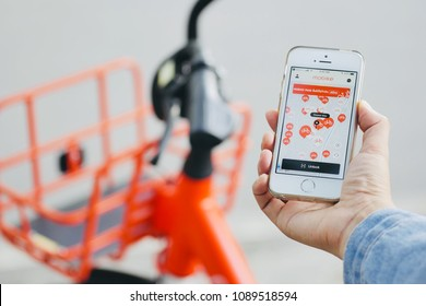 CHIANG MAI - MAY 13, 2018:  user of bike sharing project use mobike app via iPhone, blurred orange bicycle as background at chiang mai, thailand