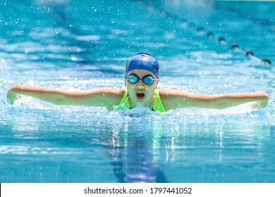 Chiang Mai, Thailand - 10 October - Young female swimmer swims her butterfly stroke during her swim practice at an outdoor swimming pool in Chiang Mai, Thailand on October 10, 2019