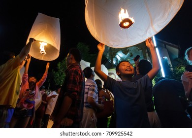 CHIANG MAI, THAILAND - 12/30/2015: A boy releases a floating lantern at a temple on New Year's Eve in Chiang Mai, Thailand.