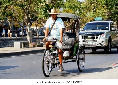 CHIANG MAI - THAILAND 17, 2009: A man rides on his rickshaw in search of customers in Chiang mai.