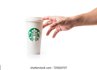 Chiang Mai, Thailand - 30 September 2017 - Male hand reaches to grab a Starbucks white paper cup on top of white table against white background in Chiang Mai, Thailand on September 30, 2017